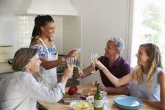 Deux couples préparant le dîner font un pain grillé à la table de cuisine Photographie stock libre de droits