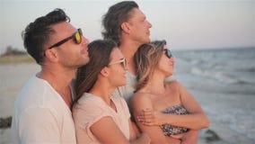 Deux couples regardent le coucher du soleil passant le temps ensemble sur le bord de la mer pendant la Windy Weather banque de vidéos
