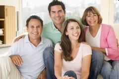 Deux couples se reposant dans le sourire de salle de séjour Photo stock