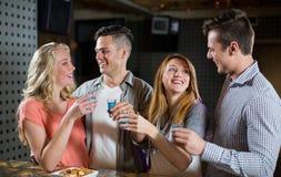 Deux couples se tenant au compteur de barre et ayant des tirs de tequila Images stock