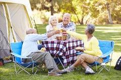 Deux couples supérieurs appréciant des vacances de camping Photos stock