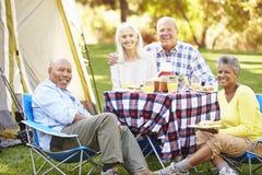 Deux couples supérieurs appréciant des vacances de camping Images stock
