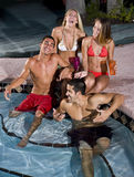 Deux couples traînant dans la piscine Photos stock