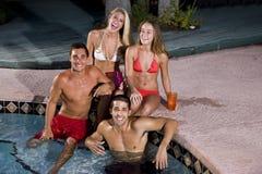 Deux couples traînant dans la piscine Images stock