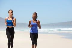 Deux coureurs féminins s'exerçant sur la plage Photographie stock libre de droits