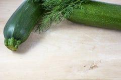 Deux courgettes crues vertes avec le fenouil sur le fond en bois clair Image stock