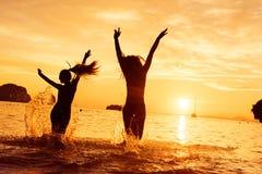 Deux courses heureuses de filles vers la mer de coucher du soleil Images libres de droits