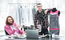 Deux couturiers travaillent ? cr?er l'habillement du ` s de femmes dans le studio photos stock