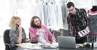 Deux couturiers travaillent ? cr?er l'habillement du ` s de femmes dans le studio photographie stock libre de droits