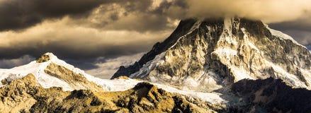 Deux crêtes de montagne couronnées de neige élevées dans la soirée s'allument avec le mauvais temps se déplaçant dedans Image stock