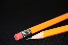 Deux crayons jaunes sur le fond brouillé de noir foncé papeterie Outil de bureau Concept d'affaires Images stock