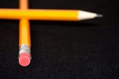 Deux crayons jaunes sur le fond brouillé de noir foncé papeterie Outil de bureau Concept d'affaires Photo libre de droits