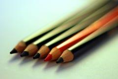 Deux crayons oranges entre les crayons noirs photo libre de droits