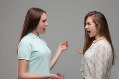 Deux cris perçants de jeunes femmes à l'un l'autre Images libres de droits