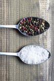 Deux cristaux de sel de witlh de cuillères en métal et grains de poivre de couleur sur la table en bois Photographie stock libre de droits