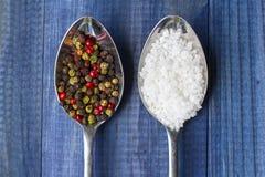 Deux cristaux de sel de witlh de cuillères en métal et grains de poivre de couleur sur la table en bois bleue Photo libre de droits