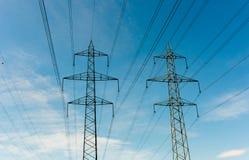 Deux croix grandes de trellis et lignes électriques à haute tension sous un ciel bleu photo libre de droits