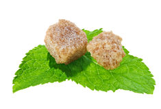 Deux cubes bruns en sucre de canne de morceau au-dessus de menthe poivrée Photo libre de droits
