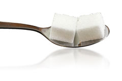 Deux cubes en sucre sur une cuillère ont isolé le fond blanc Images stock
