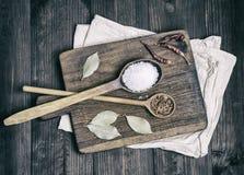 Deux cuillères en bois avec les épices et le sel blanc sur une coupe brune photographie stock