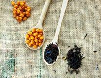 Deux cuillères en bois avec les baies saines vitaminic d'argousier et le thé noir au-dessus du fond de toile à sac Cuisson, photographie stock