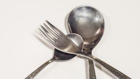Deux cuillères et fourchettes sur un fond blanc Image stock