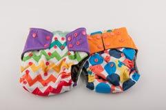 Deux culottes colorées de bébé avec le modèle et boutons s'étendent sur le fond blanc Images libres de droits