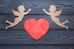 Deux cupidons et un coeur rouge fait en texture en bois Photographie stock