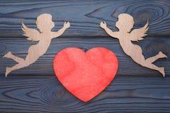 Deux cupidons et un coeur rouge fait en texture en bois Images libres de droits