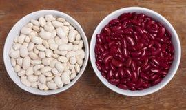 Deux cuvettes avec les haricots nains rouges et blancs Image stock