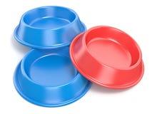 Deux cuvettes bleues d'animal familier pour la nourriture et un rouge rendu 3d Photos libres de droits