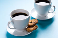 Deux cuvettes de café avec des biscuits sur le fond bleu Photo stock