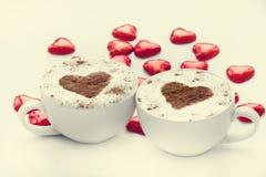 Deux cuvettes de café avec le symbole et la sucrerie de coeur autour. Photos libres de droits