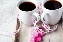 Deux cuvettes de café avec les sucreries roses Photo stock