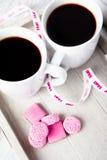 Deux cuvettes de café avec les sucreries roses Photographie stock libre de droits