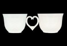 Deux cuvettes de café blanc sur le noir Photographie stock libre de droits