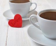 Deux cuvettes de café et d'un coeur Photos stock