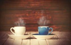 Deux cuvettes de café sur la table en bois Photos stock