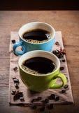 Deux cuvettes de café sur la table en bois Photographie stock libre de droits