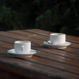 Deux cuvettes de café vides blanches de café express sur la table Photographie stock libre de droits