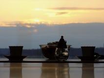 Deux cuvettes de thé dans le coucher du soleil Photos stock