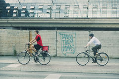 Deux cyclistes dans le milieu urbain, le rouge de port, l'autre dans le vêtement de tenue professionnelle décontractée et la chem photos libres de droits