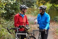 Deux cyclistes masculins mûrs sur le tour regardant le téléphone portable APP Photo libre de droits