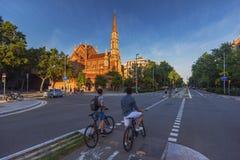 Deux cyclistes montant dans la ruelle de vélo dans la rue de Barcelone avec une église sur le fond Images stock