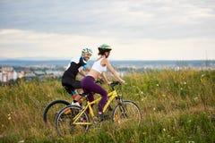 Deux cyclistes montent sur la colline dans l'herbe avec les fleurs sauvages à la distance la ville et les montagnes Photos stock