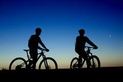Deux cyclistes sur le fond du ciel nocturne Images stock
