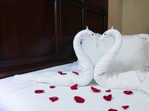 deux cygnes de serviette formés sur le lit Photos stock