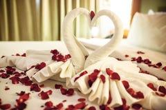 Deux cygnes faits à partir des serviettes embrassent sur le lit de blanc de lune de miel Image stock