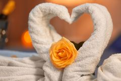 Deux cygnes faits de serviettes et fleur rose sur le fond brouillé, plan rapproché Images libres de droits