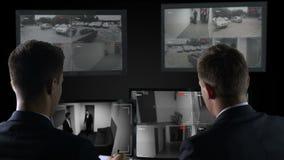 Deux détectives regardant par des disques de caméra, enquête de crime, preuves banque de vidéos